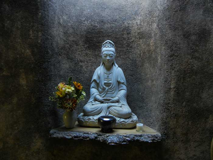 A buddha shrine in a niche inside the garden tool shed at Green Gulch