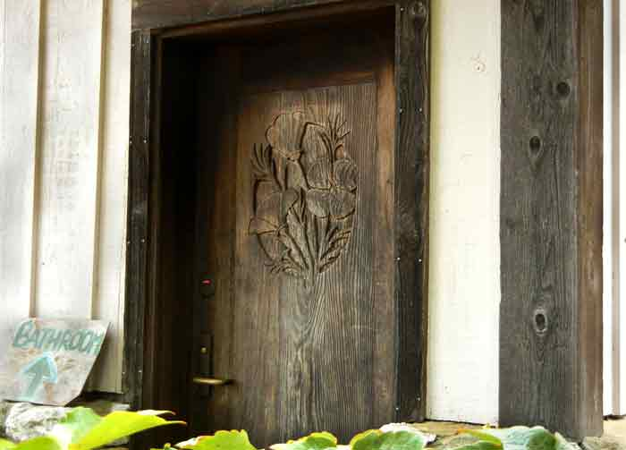 A carved wooden door adorns the building where Steven Decater build the first cookhouse on the farm at UCSC